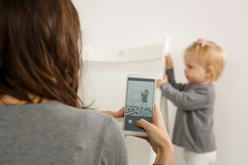 Mother taking a photo of her baby girl with a cell phone in a nursery room