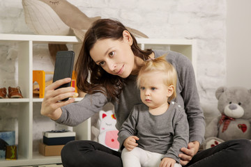 Mother taking a photo of her and her baby girl with a cell phone in a nursery room