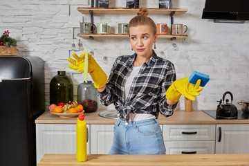 Young woman or housewife in rubber gloves wiping table with microfiber cloth at home kitchen.