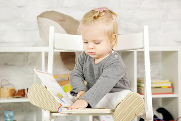 Cute baby with a book sitting on the chair
