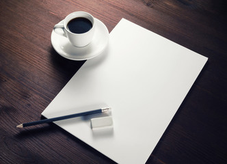 Blank letterhead, coffee cup, pencil and eraser on wood table background. Responsive design template.