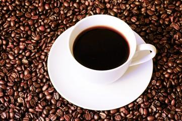 Tasse Kaffee auf Hintergrund aus gerösteten, ganzen Kaffeebohnen