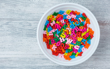 multicolored wooden letters in a plate, eating knowledge