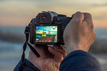 Man hands taking a photograph with DSLR of sunset landscape