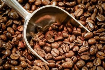 Aromatische, geröstete Kaffeebohnen mit Kaffeeportionierer, Hintergrund