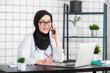 portrait of beautiful muslim female doctor using mobile phone