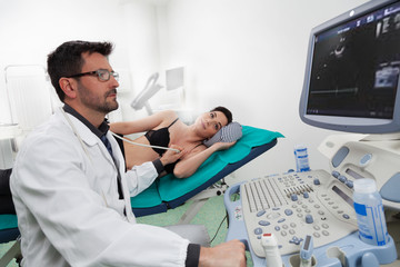 A doctor listening his female patient with a ultrasound ecography