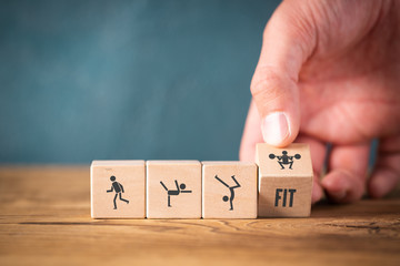 Icons on cubes symbolizing sports on wooden background