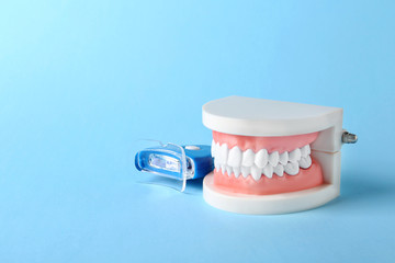 Educational model of oral cavity with teeth and whitening device on color background. Space for text