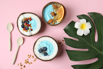 Flat lay composition with yummy spirulina smoothie in coconuts on color background