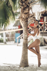 Tanned beautiful and sexy girl is wearing white swimsuit near the palm tree on the beach of Zanzibar