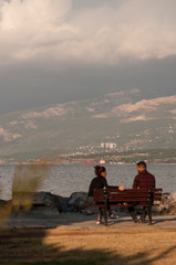 Iskenderun, Hatay, Turkey November 16, 2016: a young couple a man and a woman Europeans are having a conversation sitting on a bench at the seashore in autumn on a sunny day