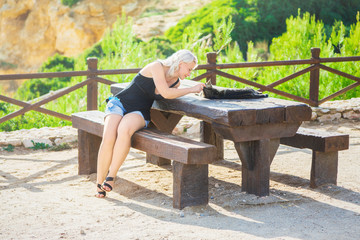 Girl playing with cat on picnic table