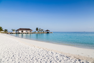 Water villas on the clear blue beach in the Maldives