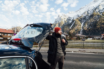 Bearded man taking his backpack out of the car trunk overlooking the mountains in Mittenwald, Germany