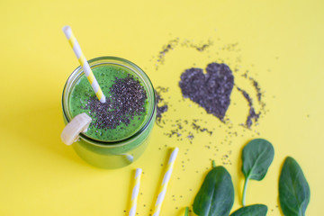 Green spinach smoothies in jar with heart pattern of chia seeds, healthy food concept, breakfast, yellow background, Valentine's day