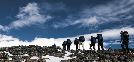 Group of people in a line hiking up the highest mountain in Sweden, Kebnekaise during a climb to reach the peak.