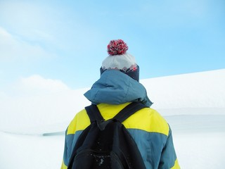 a boy in a colorful jacket, a cap with a bubo and a backpack on his shoulders against the backdrop of a snowy mountain and a winter blue sky. Back view