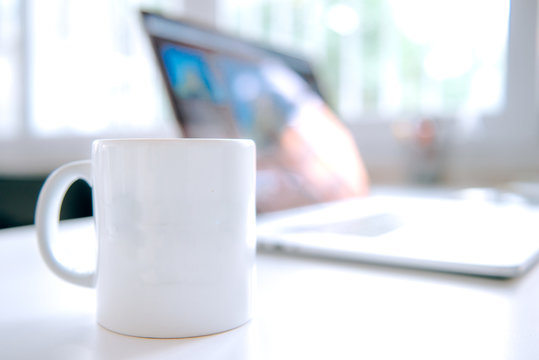 cup of coffee and laptop on the table. Coffee  mug and notebook on the table in office working interior.
