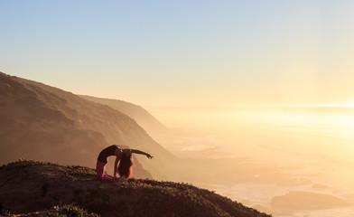 Woman doing a yoga pose on a mountaintop