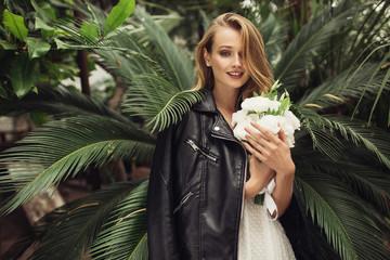 Young pretty smiling woman in white dress with black leather jacket on shoulders holding little bridal bouquet of flowers in hands happily looking in camera while spending time in cozy greenhouse