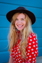 Woman wearing a polka dot shirt and black slouch hat