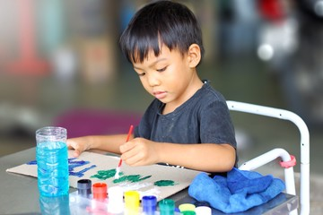 Kid and education concept, In the classroom, a student child boy drawing and painting colors on the paper.