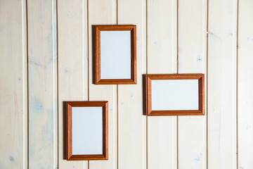 empty photo frames and paintings on the background of a wooden wall