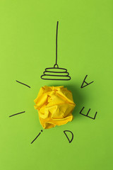 Composition with crumpled paper ball, drawing of lamp bulb and word IDEA on color background. Creative concept