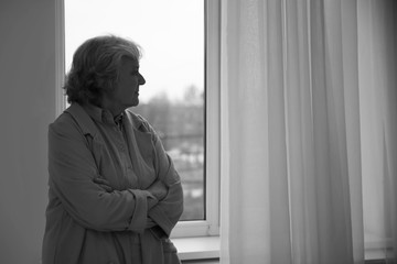 Portrait of elderly woman near window indoors, space for text. Black and white effect
