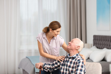Elderly man with female caregiver at home. Space for text