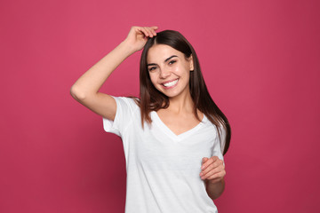 Portrait of young woman laughing on color background Wall mural
