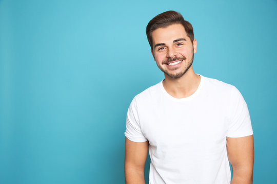 Portrait of young man laughing on color background. Space for text