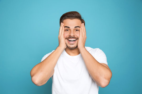 Portrait of young man laughing on color background