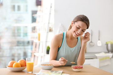 Young woman in fitness clothes having healthy breakfast at home