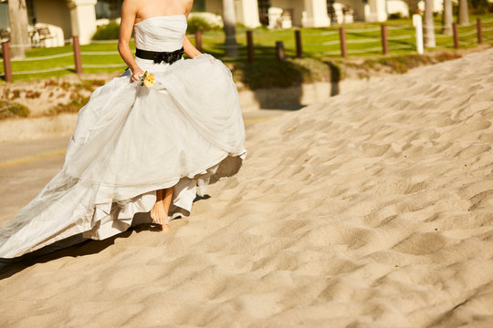 Low section of bride in wedding dress running on beach