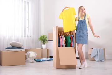 Young emotional woman near wardrobe box at home