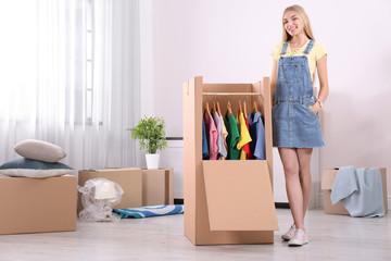 Young woman near wardrobe box at home