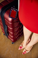 woman in red dress with suitcase and luggage tag