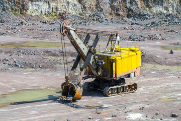 A large tracked excavator in a quarry open pit mining of granite stone. Process production stone and gravel. Quarry mining equipment.