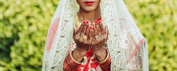 Hindu bride in white veil raises her hands up