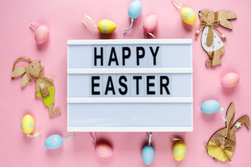 Happy Easter text on lightbox on pink pastel paper background with yellow, pink, blue eggs and bunnies. Bright template for Easter, top view, flat lay, holiday background with copy space