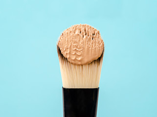 pouring liquid beige makeup foundation on a brush makeup.