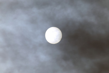 solar disk at noon through the clouds
