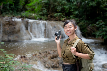 Female hikers take pictures of themselves with beautiful waterfalls. Relax after hiking