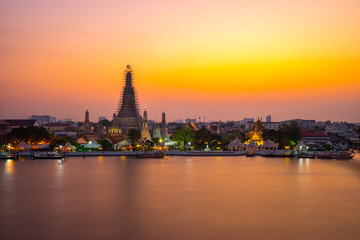 Wat Arun Temple Beside Chao Phraya River at Twilight Time in Bangkok, Thailand. One of the Most Famous Place of Thailand's Landmarks. Beautiful Sunset Sky with Smooth Water.