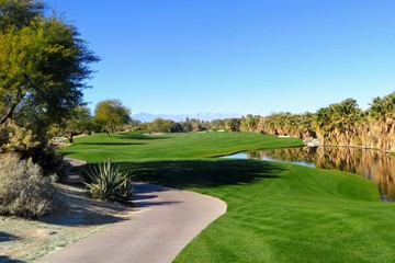 A beautiful view of a par 5 with the  desert surrounding the hole as well as a pond.  The golf course is in Palm Springs, California, United States.  A golf oasis.