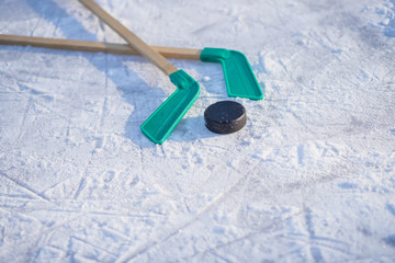 ice hockey stick with white tape and puck. team game, competition concept in business.Ice hockey sticks and puck, equipment for kids hockey player in winter game season.Winter activity.