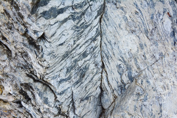 The texture of old stone wall. It is a beautifull natural patterned surface with white and gray