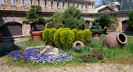 Sunny day in a spring garden with clay pots, trees, bushes and blossoming flowers- concept of lifestyle and leisure